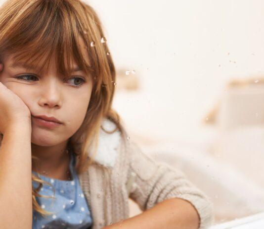 λυπημένο παιδί στο παράθυρο